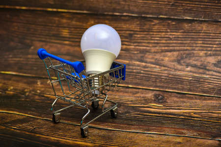 An economical lamp on a trolley in a consumer basket, a simple lamp lies nearby. The concept of choosing savings and energy saving.