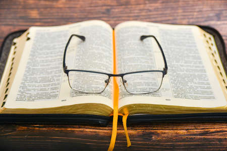 The Bible and glasses, glasses for sight lie on the opened Bible of a gift issue with gilded pages.