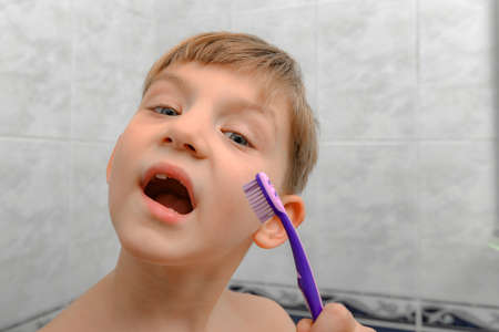 The child in the shower room, the boy holds a toothbrush in his hand.
