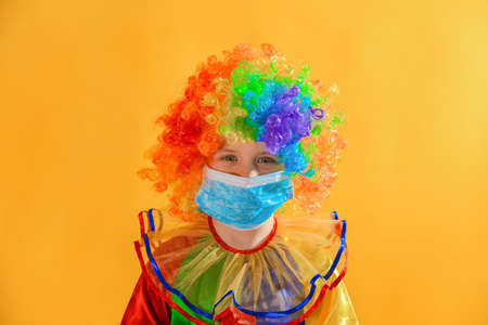 Sad and sad baby clown in a protective medical mask from coronavirus on a yellow background.