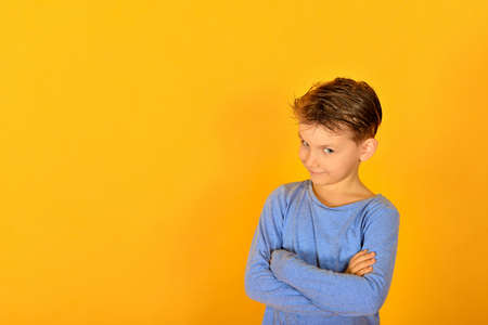 Glamorous and stylish boy posing for the camera, model in blue clothes in the studio on a yellow background. Фото со стока