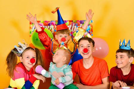 Clown child and joyful children at a festive event. Фото со стока