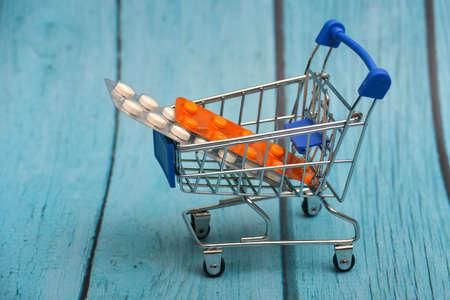 Cart with medicines, pills, antibiotics, vitamins, antiviral agents in a consumer basket.