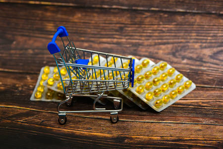 Empty consumer trolley on yellow drugs background on brown wooden background. Фото со стока