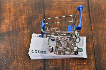 Dollar in a trolley, money in a consumer basket.