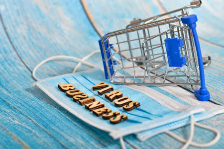 The inscription virus and business in wooden letters on a protective mask on a blue background. An empty overturned cart lies nearby.