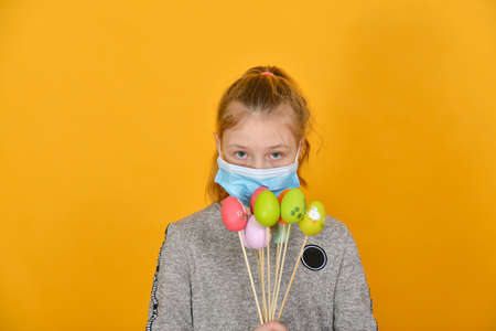 A girl in a protective mask from a coronavirus holds Easter eggs in her hand on a holiday.