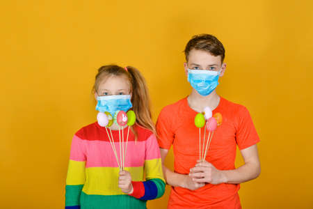 A boy with a girl in a protective mask from a coronavirus give each other Easter eggs on a holiday. Фото со стока