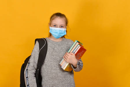 Schoolgirl in a protective mask against coronavirus with textbooks in hand, concept of quarantine and home teaching.