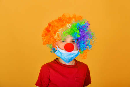 A child clown in a protective mask urges you to carefully examine the signs of coronavirus. 스톡 콘텐츠
