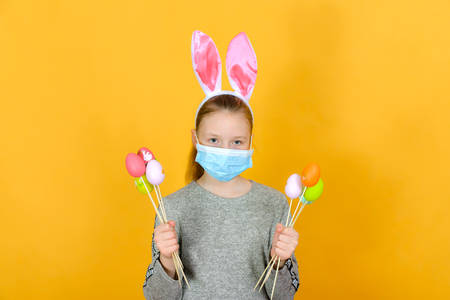 A girl with rabbit ears and a protective mask against coronavirus holds Easter eggs in her hand on a holiday.