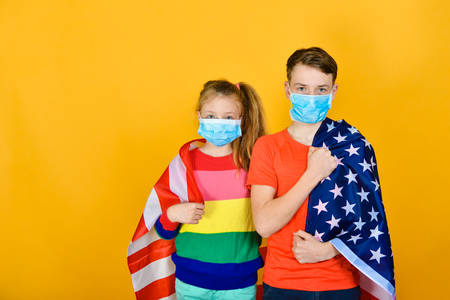 A boy with a girl in a protective mask from a coronavirus sheltered by the American flag. The concept of protection and patronage of the United States.