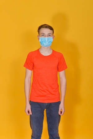 A teenager is standing in a protective mask on a yellow background. Children and personal protective equipment. Фото со стока