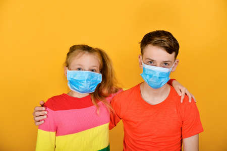 Boy with a girl in a protective mask against coronavirus, children on a yellow background against the virus.