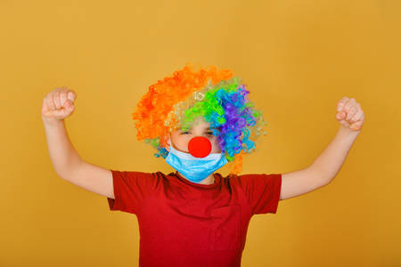 A child clown in a protective mask urges you to carefully examine the signs of coronavirus. 版權商用圖片