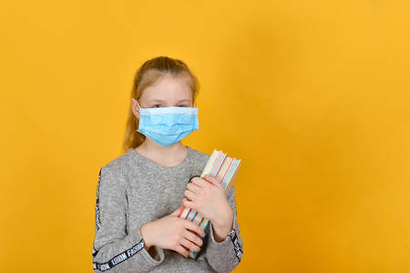 Schoolgirl in quarantine in a protective mask and with textbooks in hand. Фото со стока