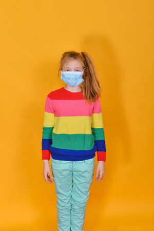 Girl standing in a protective mask on a yellow background. Children and personal protective equipment....