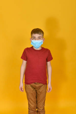 A boy is standing in a protective mask on a yellow background. Children and personal protective equipment.