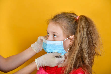 A doctor in medical gloves examines a girl in a protective mask for signs of coronavirus.