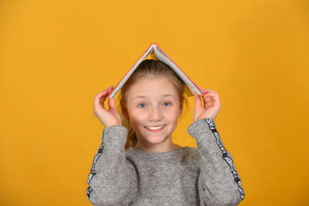 Joyful and cheerful girl holds a book over her head