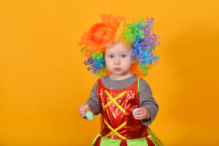 A small child, a girl in a clown wig, holds Easter eggs in her hands