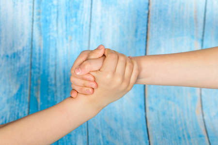 Friendly people shaking hands on a blue wooden background