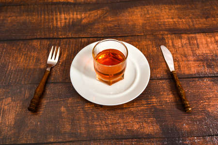 A glass of cognac stands on a plate, alcohol instead of food, the concept of alcohol dependence.