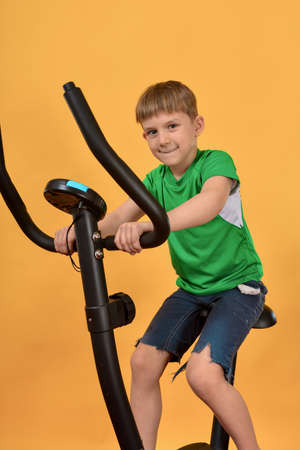 The boy goes in for sports, the child on a stationary bike does cardio and looks forward to the camera.