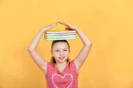 Girl holds books on her head and raises her hands to the top, student child on a yellow background.