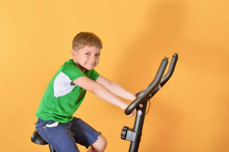 The child goes in for sports on a stationary bike.