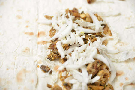 Cabbage sprinkled on meat and laid on pita bread.