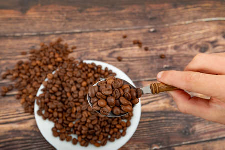 A man holds roasted coffee grains in a tablespoon on a background of a white plate and dark wood