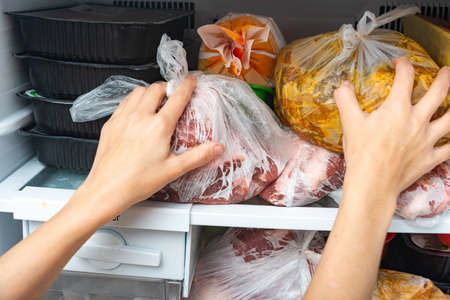 A woman takes out and puts frozen food in a freezer for long storage.