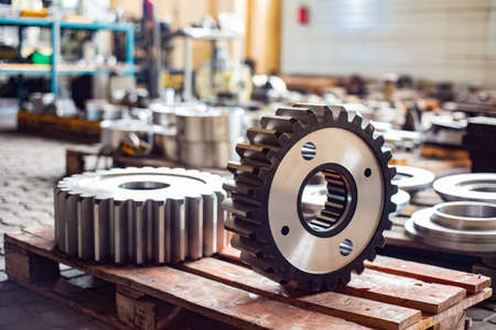 Two large gears after heat treatment lie on a wooden rack. Gear cutting and milling in heavy industry