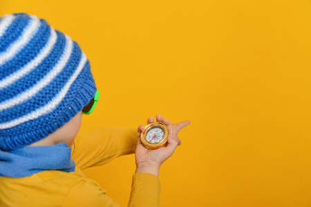 The boy in the hat and scarf looks at the compass and pokes the polish where he needs to go.