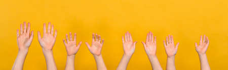 Children raise their hands up on a yellow background