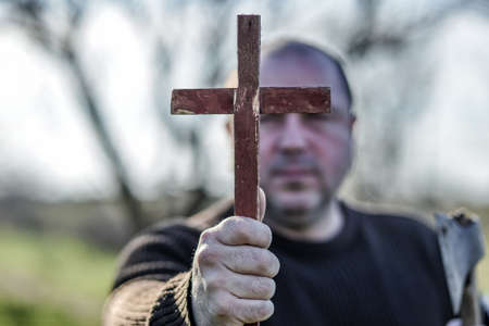 A man holds a wooden Christian cross in front of him, an ax in his other hand. The concept of casting out demons on Halloween. Stock Photo
