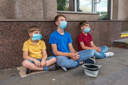 Three children wearing protective masks sit outside asking for financial assistance during the covid-19  pandemic crisis