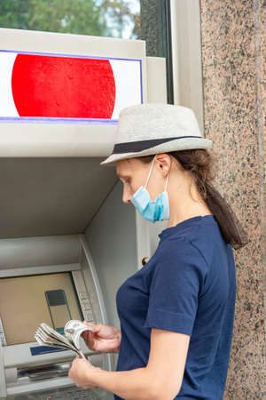 A girl in a protective mask is counting dollar bills near the ATM.