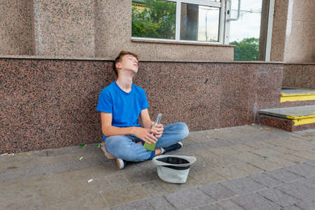 Drunk teenager with alcohol in his hands is sleeping sitting on the street and begging.