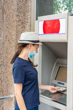 A girl in a protective medical mask withdraws cash from an ATM. Stockfoto