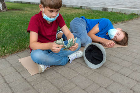 The boy counts the money begged from passers-by on the street. Stockfoto