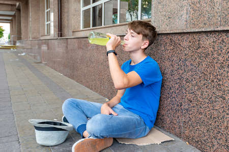 A teenager on the street drinks beer and asks for money.