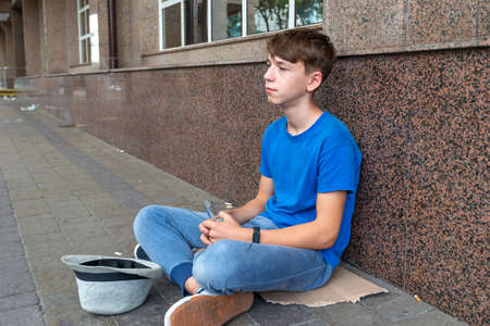 A teenage beggar sits on the street with a bottle of beer.