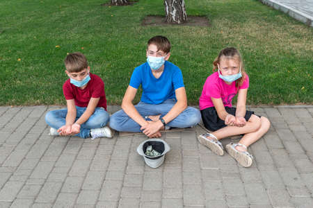 Three children wearing protective masks ask for help from passers-by during the covid 19 quarantine