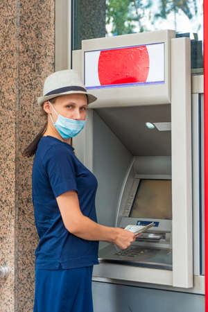 The girl in a protective mask holds money near the ATM.