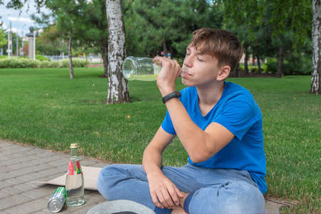 A teenager drinks alcohol while sitting on the street. Stockfoto