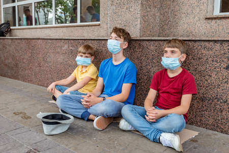 Three children wearing protective masks sit outside asking for financial assistance during the covid-19 coronavirus pandemic crisis