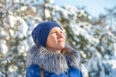 A woman in warm clothes looks up in the park in winter Stockfoto