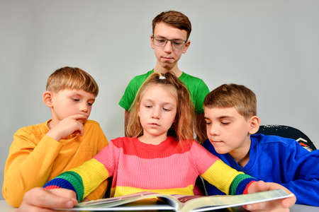 Three brothers and a sister thoughtfully read a book.